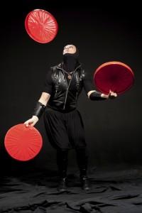 Actor in black costume juggle big red disks